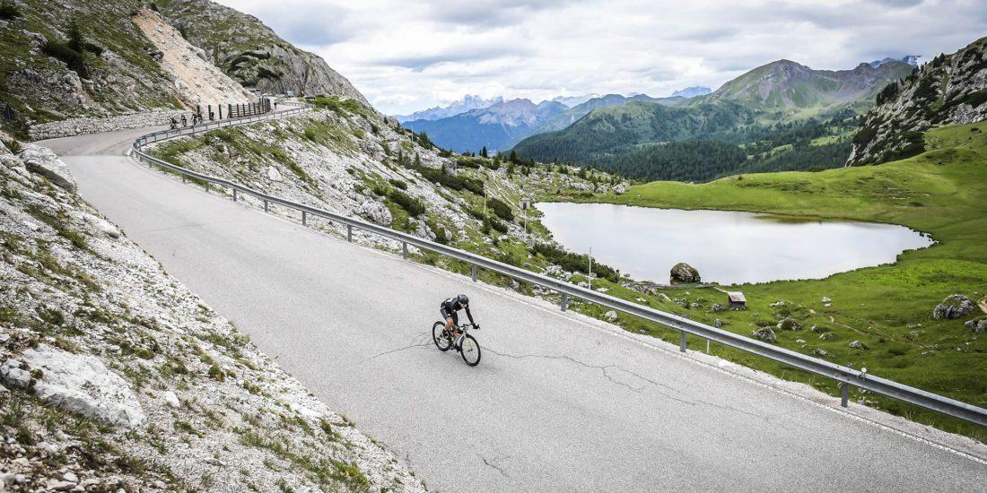 ciclista in discesa lungo passo falzarego